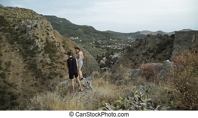Happy couple cheering and running in nature. Hiking man and woman raising arms excited in celebration outdoors.