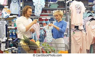 Happy couple choose infant clothes in the shopping center.