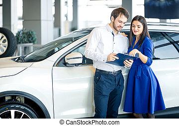 Happy couple choosing a car in dealership