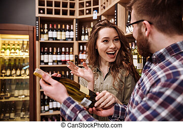 Happy couple choosing bottle of wine