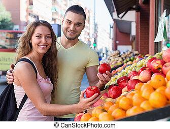 Happy couple choosing fruits