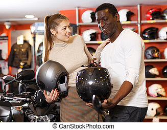 couple choosing motorcycle accessories and riding gear