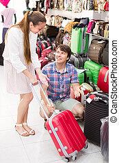 Happy couple choosing suitcase