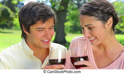 Happy couple clinking their glasses of red wine