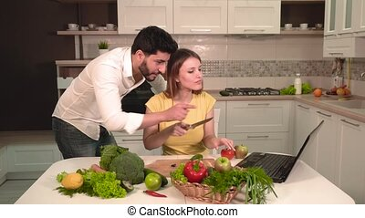 Happy Couple Cook with Laptop