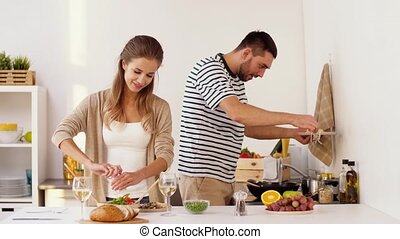 happy couple cooking and serving food at home