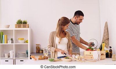 happy couple cooking food at home kitchen - people and...