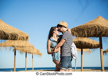 Happy couple cuddling on beach looking at each other