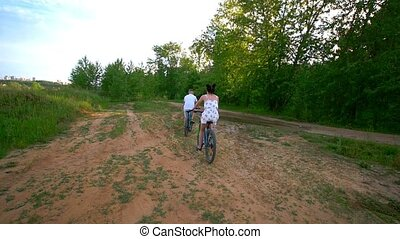Happy couple cycling on the path in the pine forest, slow-motion