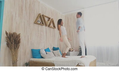 happy couple dance on bed at home