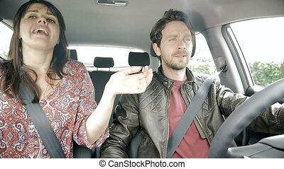 Happy couple dancing like crazy while driving car slow motion
