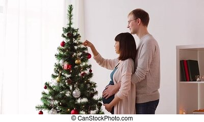 happy couple decorating christmas tree at home - pregnancy,...