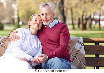 Delighted positive man hugging his wife