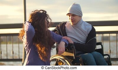 Happy couple - disabled man in wheelchair talking with attractive young woman enjoing the sunset