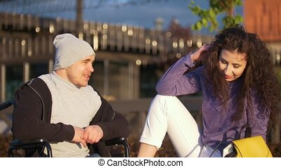 Happy couple - disabled young man in a wheelchair with young woman enjoying the sunset together