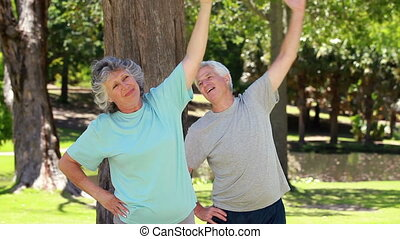 Happy couple doing fitness exercises in the countryside