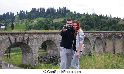 Happy couple doing selfie in front of the old viaduct