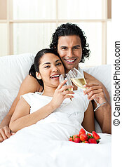 Happy couple drinking Champagne with strawberries