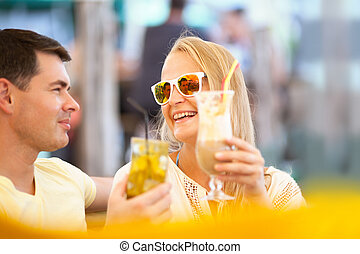 Happy couple drinking cocktails outdoor
