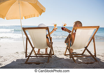 Happy couple drinking cocktails while relaxing on their deck chairs