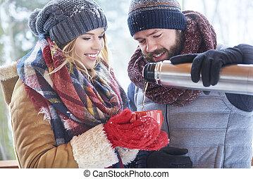 Happy couple drinking hot tea in winter