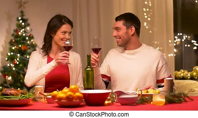 happy couple drinking red wine at christmas dinner
