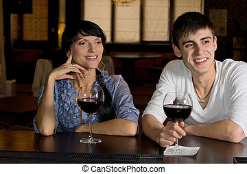 Happy couple drinking red wine at the bar