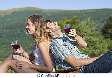 Happy couple drinking wine on a hiking trip
