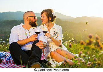Happy couple drinking wine on picnic