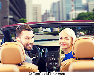 happy couple driving in cabriolet car over city