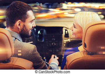 happy couple driving in car over night city