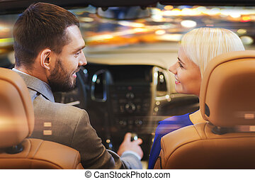 happy couple driving in car over night city - love, luxury,...