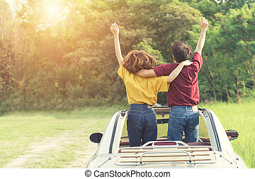 Happy Couple Driving on Country Road into the Sunset in Classic Vintage Car. Travel concept.