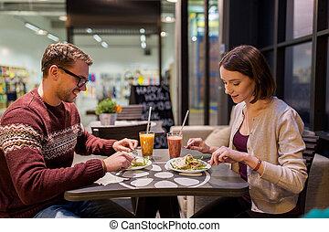 happy couple eating dinner at vegan restaurant - eating, ...