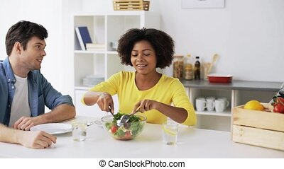 happy couple eating vegetable salad at home