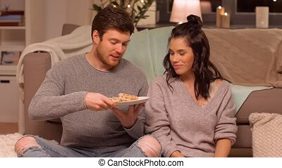 happy couple eating waffles at home - hygge, leisure and...