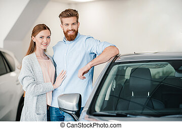 Happy couple embracing and standing at car in dealership salon