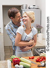 Happy couple embracing while preparing food in kitchen