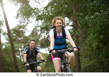 Happy couple enjoying a bike ride in nature - Portrait of a ...