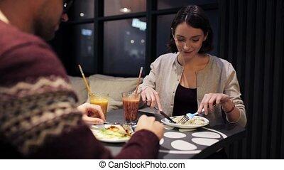 happy couple enjoying dinner at vegan restaurant - eating,...