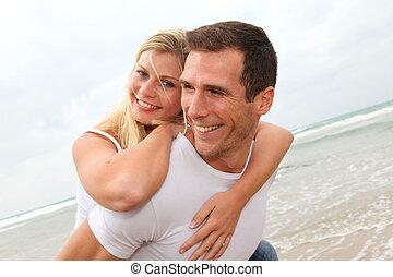 Happy couple enjoying vacation on a sandy beach