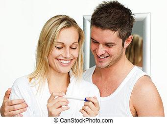 Happy couple examining a pregnancy test in bathroom