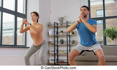 happy couple exercising and doing squats at home - sport, ...