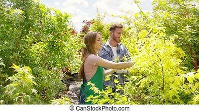 Happy couple exploring plants in garden