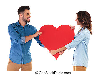 happy couple fighting over a big red heart