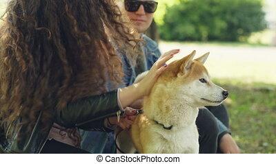 Happy couple girlfriend and boyfriend are patting cute puppy...