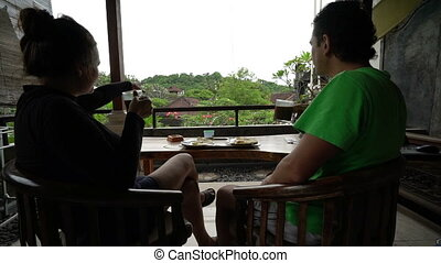 Happy couple have a breakfast on the terrace at beautiful island bali indonesia, wonderful background, family sitting on a balcony, holidays, vacation