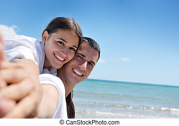happy couple have fun on the beach
