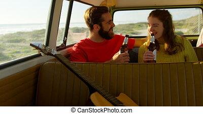Happy couple having beer in the van 4k - Happy couple having...