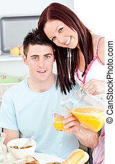 Happy couple having breakfast in the kitchen